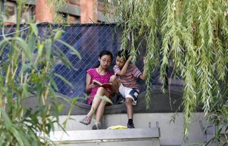 Karen Cheng, 13, and Mike Huang, 9, both of Chinatown, read along the Greenway in their neighborhood.